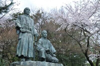 円山公園内の坂本龍馬と中岡慎太郎の銅像と桜。坂本龍馬と中岡慎太郎の墓は、円山公園からほど近い、京都霊山護国神社にある