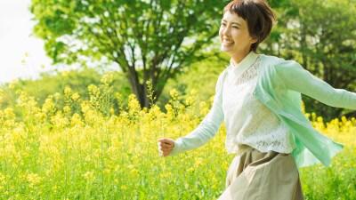 菜の花畑を駆け抜ける女性