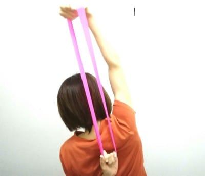背後でゴムリングを握り、片方の肘を伸ばしながら体を横へ少し倒し肩こり予防をしましょう