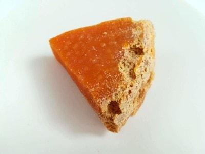 ミモレットの表面には、粉ダニによる穴やかじられたチーズの粉がついています。オレンジ色の部分を食べます