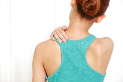 肩を抑える女性